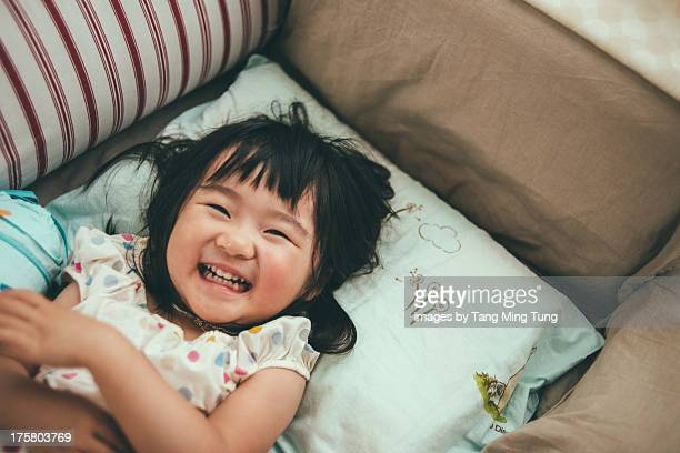 Toddler girl on bed looking into camera smiling