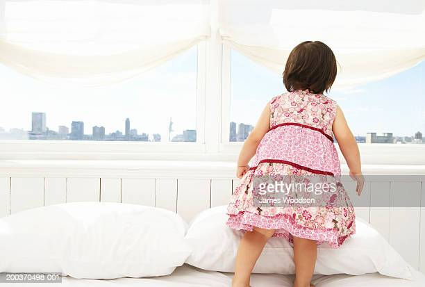 Toddler girl (21-24 months) on bed looking out window, rear view