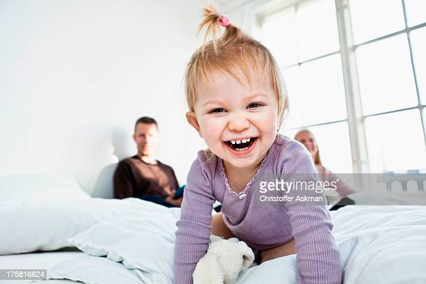 Toddler girl on parent's bed looking at camera, laughing