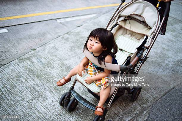 Toddler girl on stroller leaning on front handle