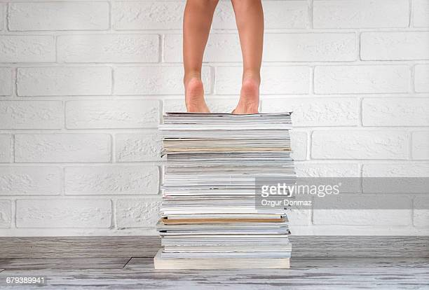 Toddler girl on tiptoes standing on magazines
