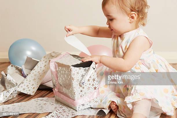 toddler girl opening birthday present - first birthday imagens e fotografias de stock