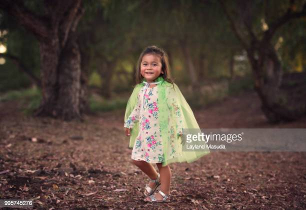 Toddler Girl Outdoors Wearing Green Cape