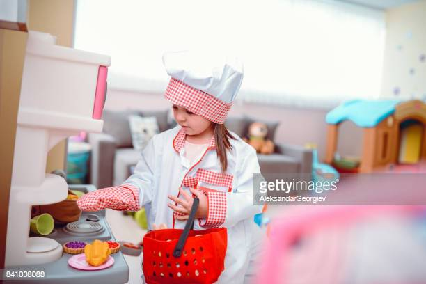 Toddler Girl Playing Cooking Chef in a Preschool Classroom