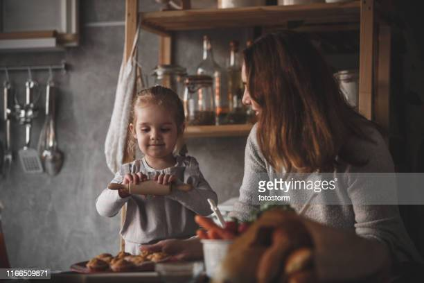 Toddler girl playing next to her mother that is preparing food in the kitchen