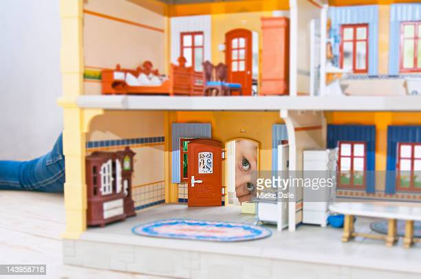 Toddler girl playing with a doll's house