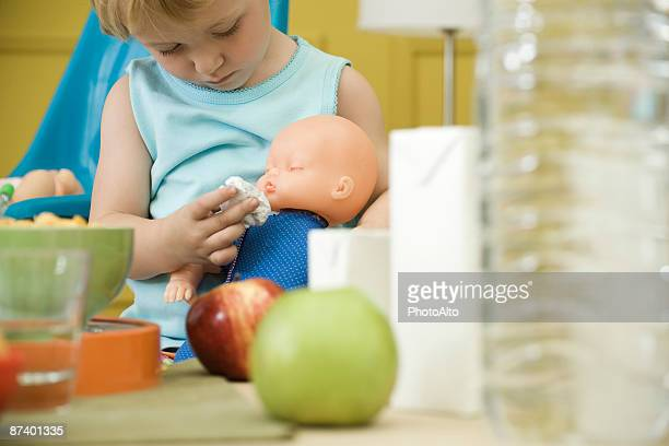 Toddler girl playing with baby doll at table