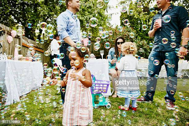 Toddler girl playing with bubbles at party