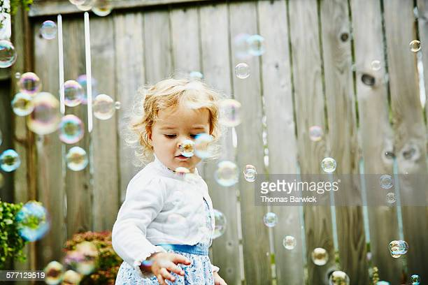 Toddler girl playing with bubbles during party