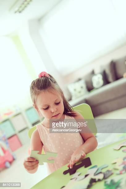 Toddler Girl Playing with Puzzle Pieces in Preschool Classroom