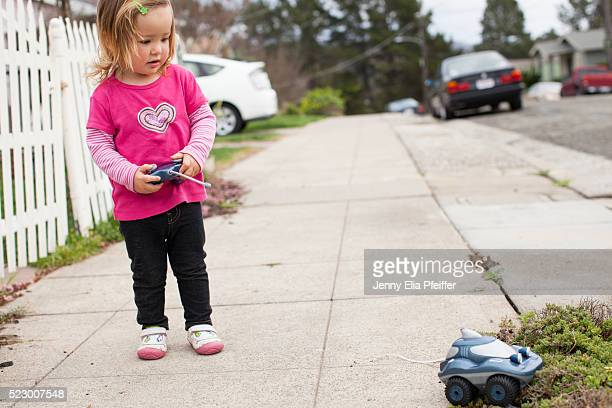 toddler girl (2-3) playing with remote control car on sidewalk - remote control car games stock pictures, royalty-free photos & images