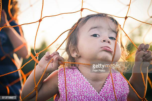 Toddler girl playing with soccer net.