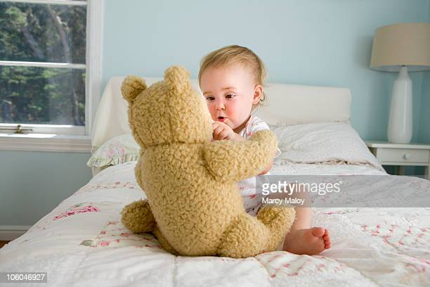 Toddler girl playing with teddy bear on bed.