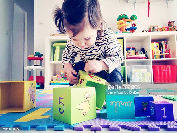Toddler Girl Playing With Toy Blocks At Home