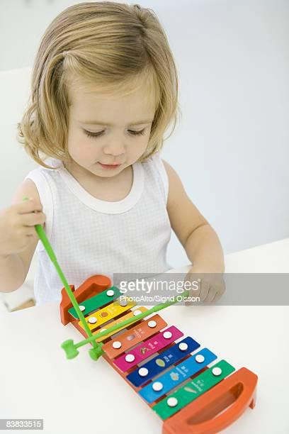 Toddler girl playing xylophone, high angle view