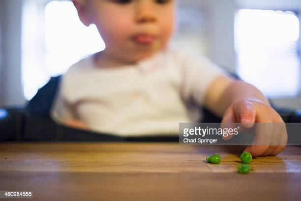 Toddler girl pointing at peas