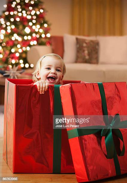 Toddler girl popping out of gift box