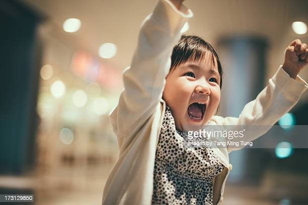 Toddler girl raising arms in the air laughing