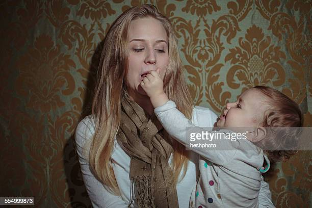toddler girl reaching for mothers mouth - heshphoto stock pictures, royalty-free photos & images