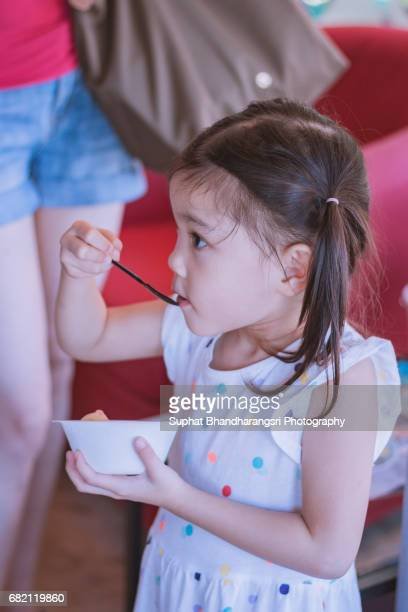 Toddler girl refreshing herself with ice cream