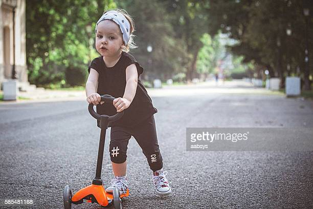 Toddler girl riding push scooter on pavement.