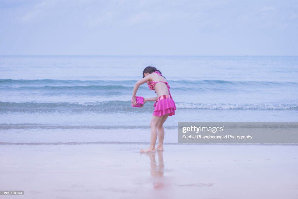 Toddler girl rinsing the sand toy : Stock Photo