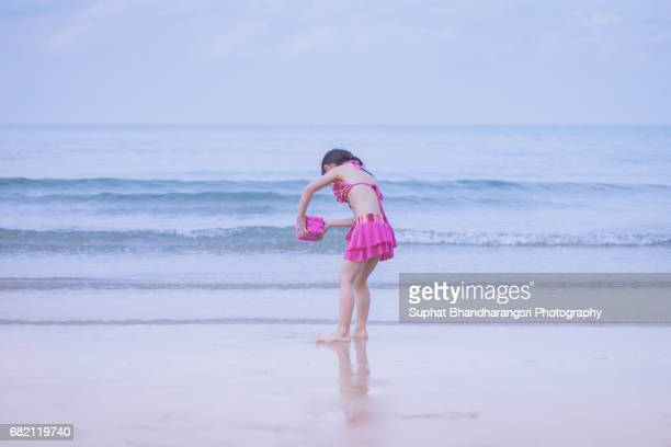 Toddler girl rinsing the sand toy