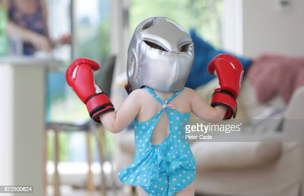 Toddler girl running around house in swimming costume and boxing clothes