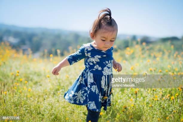 Toddler Girl Running In Spring Flowers Meadow