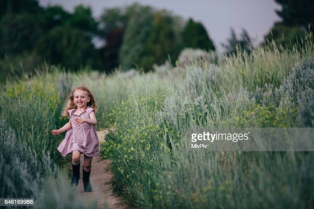 Toddler girl running on a path in a field of green tall grass