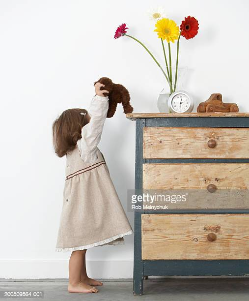 Toddler girl (18-21 months) setting teddy bear atop dresser, side view
