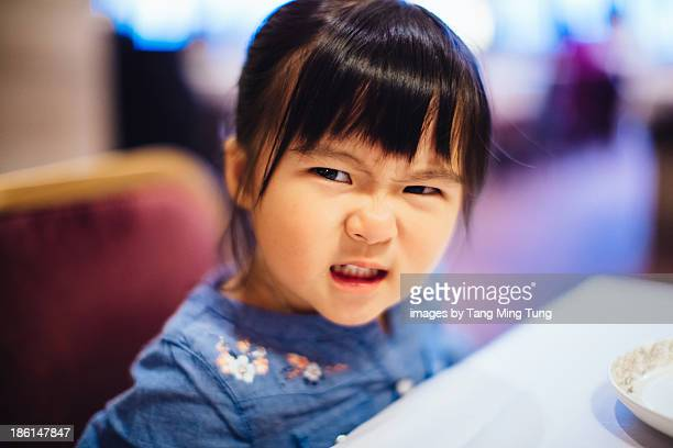 Toddler girl showing angry face in restaurant