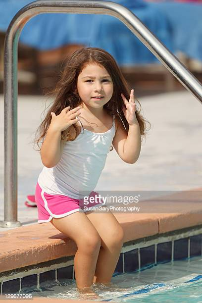 Toddler girl sits at pool