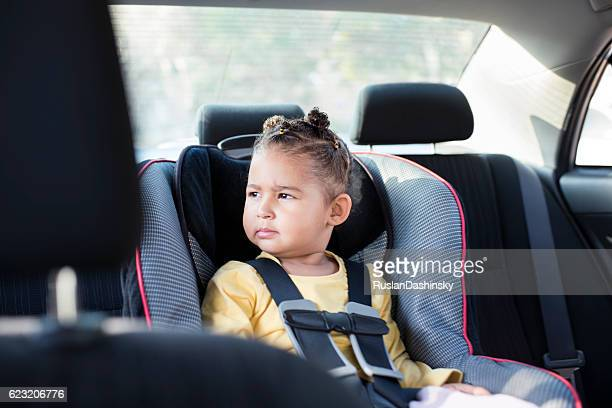 Toddler girl sitting in safety car chair.
