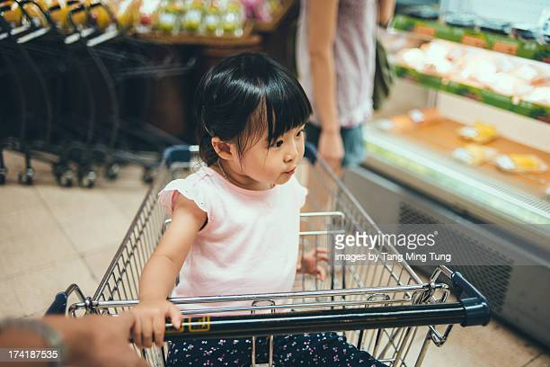 Toddler girl sitting in trolley in supermarket