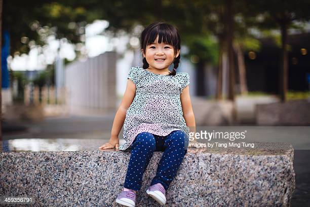 Toddler girl sitting on a stone bench in park