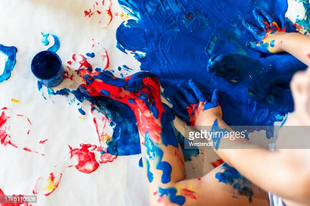 toddler girl sitting on paper on the floor playing with finger paint, partial view - finger painting stock pictures, royalty-free photos & images