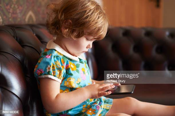 Toddler girl sitting on sofa using smartphone