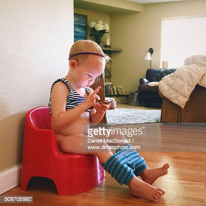 Toddler Girl Sitting On Training Toilet While Using A