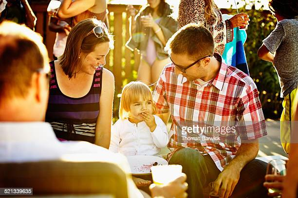 Toddler girl sitting with parents during party