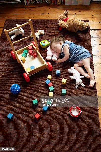 toddler girl (18 months) sleeping on rug - richard drury stock pictures, royalty-free photos & images