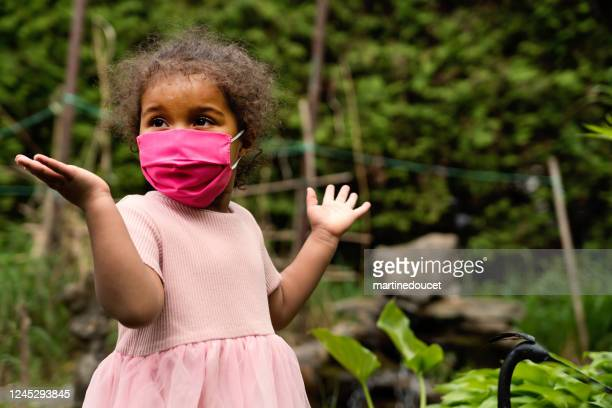 toddler girl smiling behing stylish protective mask. - preschool child stock pictures, royalty-free photos & images