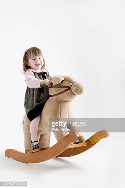Toddler girl (21-24months) smiling on rocking horse, portrait
