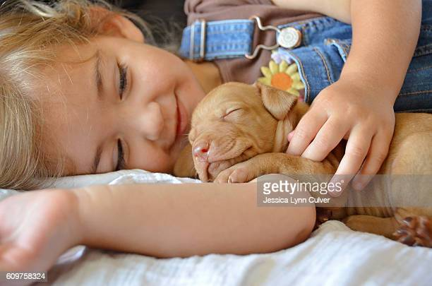 Toddler girl smiling sweetly at puppy dozing in her arms