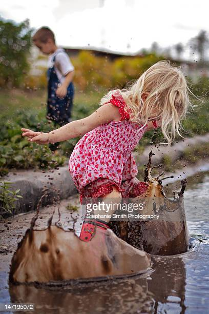 Toddler girl splashing in mud