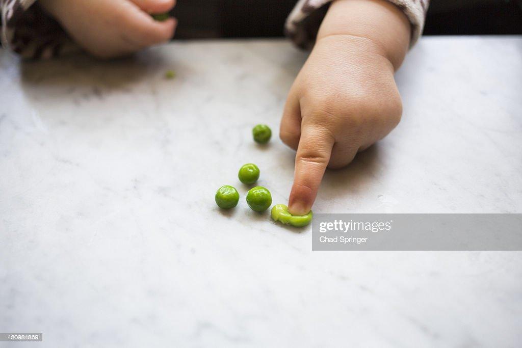 Toddler girl squashing pea : Stock Photo