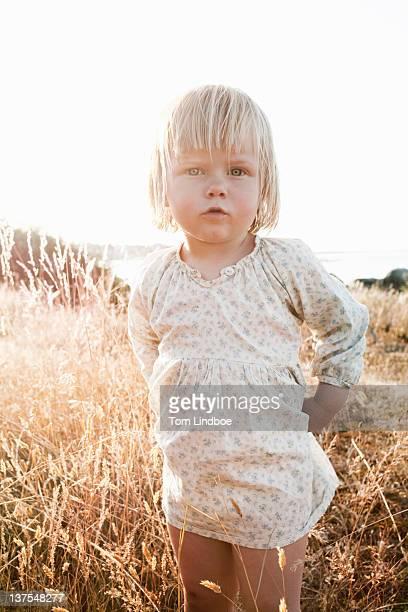 Toddler girl standing in wheatfield