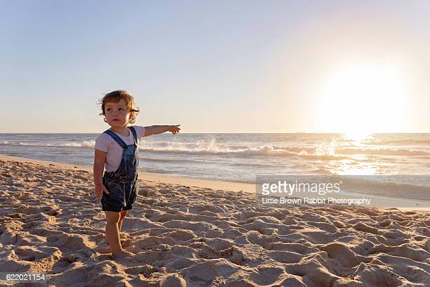 toddler girl standing on the beach at sunset and pointing towards the ocean - rabbit beach stock photos and pictures