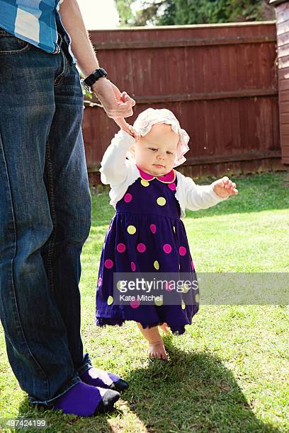 toddler girl taking her first steps - 出来事の発生 ストックフォトと画像