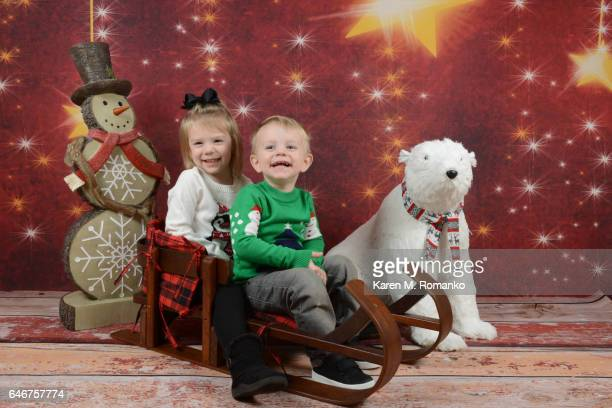 Toddler girl & toddler boy in Xmas sweaters smiling sitting on wooden sled, with snowman and plush polar bear